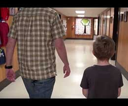 A father and son walking side by side through a hallway