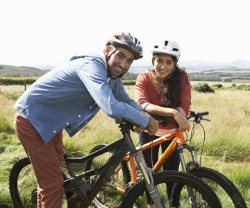 A young man and woman riding mountain bikes and wearing helmets outside on a sunny day.